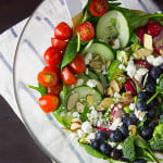 a bowl of salad made with tomatoes, cucumber, broccoli, blueberries, and almonds