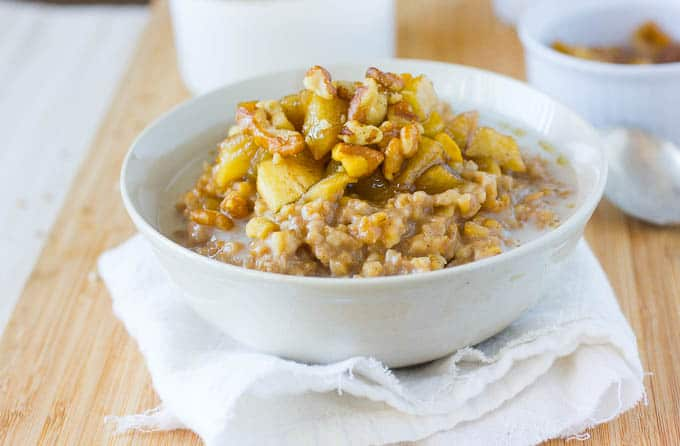 A bow of steel cut oatmeal topped off with apples.