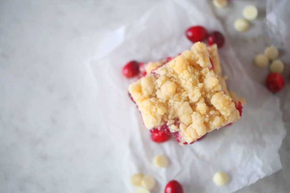 Cranberry and white chocolate bars surrounded by cranberries and white chocolate chips