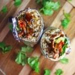 a burrito with rice, pork, carrots, cucumber, cilantro, and radishes