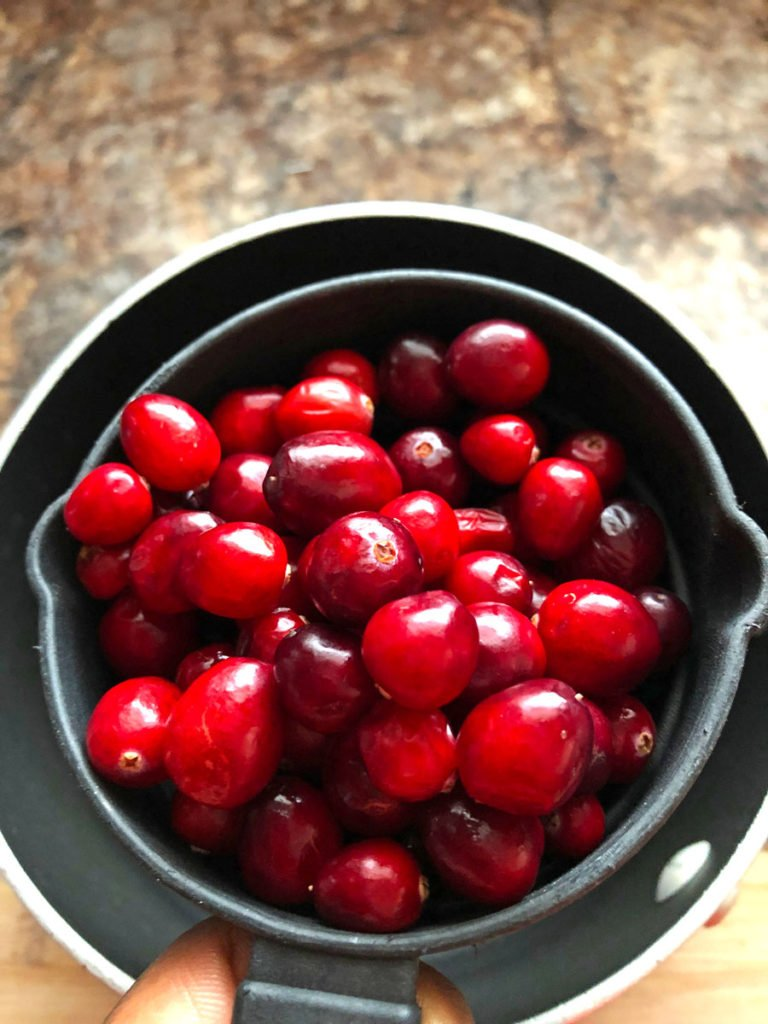 A measuring cup of fresh cranberries