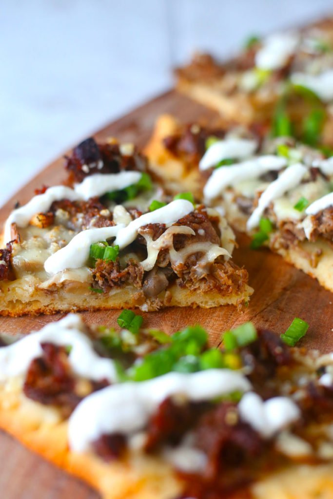 steak and mushroom pizza on top of butting board