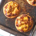 A sheet pan with pulled pork pizzas and melted cheese