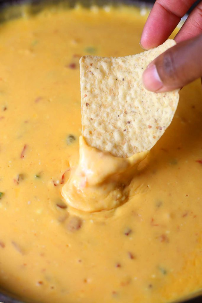 Loaded Beer Cheese Skillet Dip in bowl being scooped by a chip